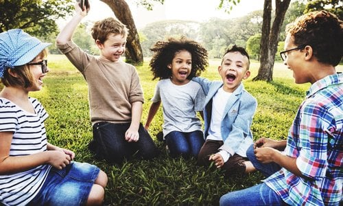 Diverse group of kids playing outside in a circle