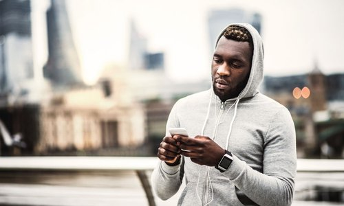Hip athletic man stopping on city bridge to send a quick text