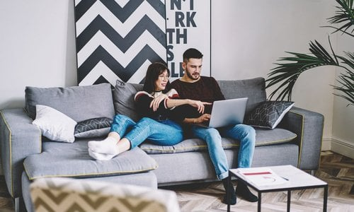 Couple in modern living room looking at laptop