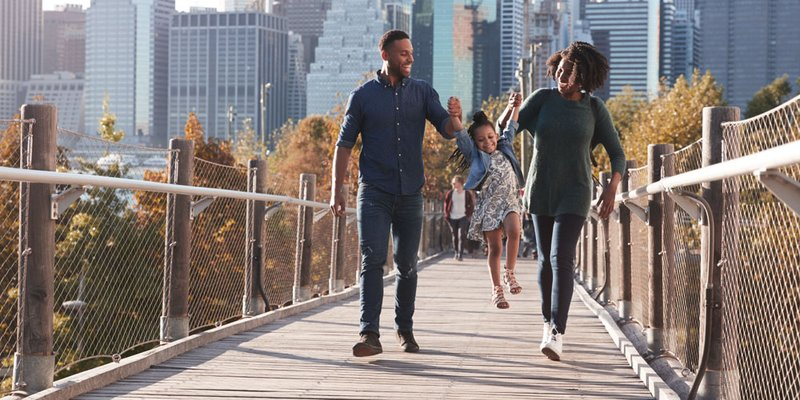 Family walking together on bridge with cityscape in the background