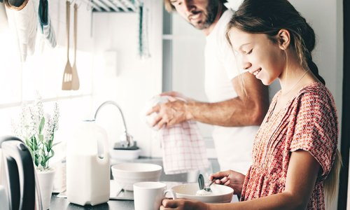 Dad and daughter cooking together in nice bright kitchen