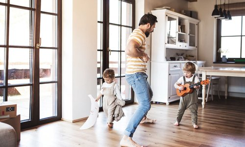 Daddy and his two toddlers rock out in the kitchen as toddler plays a tiny ukulele
