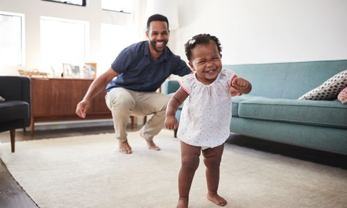 Proud papa watches baby girl learn to walk in living room