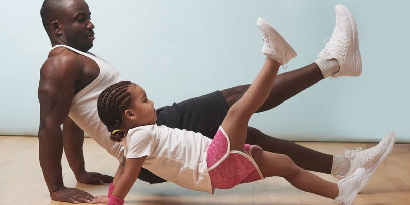Daddy and daughter working out together at home