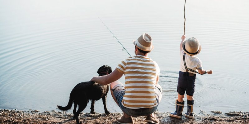 Dad and son in matching hats fish together with their dog at a nice still pond