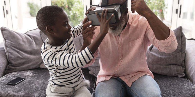 Grandson helps grandpa with virtual reality headset in living room