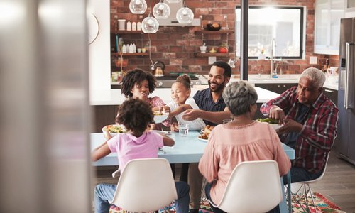 Multi-generational family enjoying a meal together at kitchen table