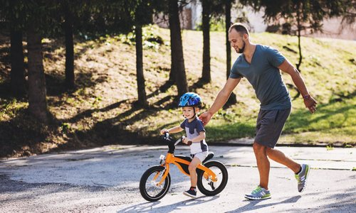 Dad helps his son learn how to ride a bike