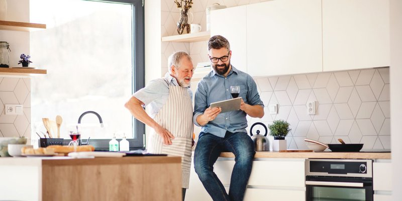 Grown man showing his father something on his phone in bright modern kitchen