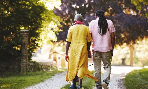 Grown man walking with his mother down a quiet street road
