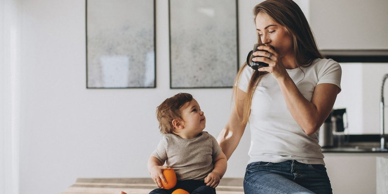 Mom enjoys a cup of coffee while lovingly looking at her cute baby son