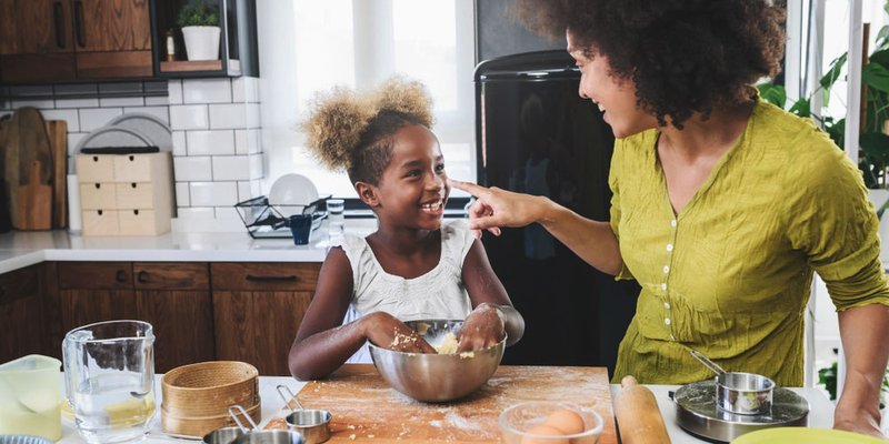 Mom and daughter baking together at kitchen island