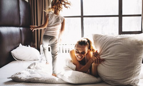 mom and daughter jumping on the bed