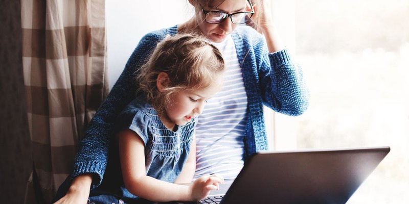 mom and toddler sitting at windowsill working on laptop together
