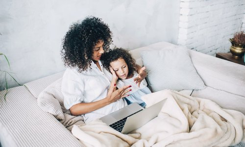 mom and daughter snuggle on couch in bright modern living room