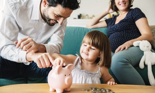 family teachers their daughter about money and help her put coins in her little piggy bank