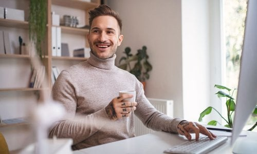 Man working on his laptop in bright modern coworking space