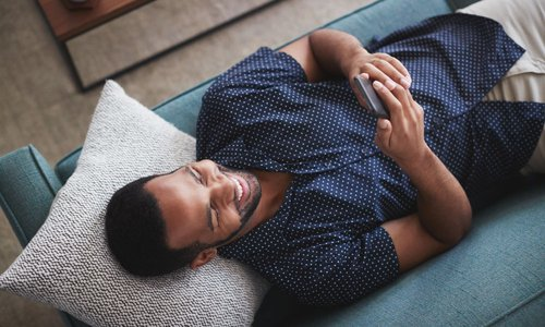 Well dressed man relaxing on his couch and sending a text on his mobile device