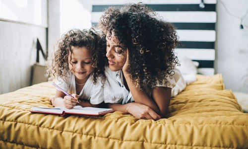 Mom and daughter write in their journal together while laying in bed