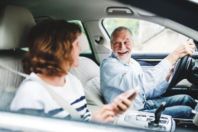 Older gentleman driving and happily chatting with his passenger