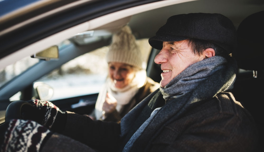 Senior couple in car dressed in fashionable, modern winter gear