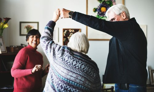 Cute seniors having a dance party in their living room