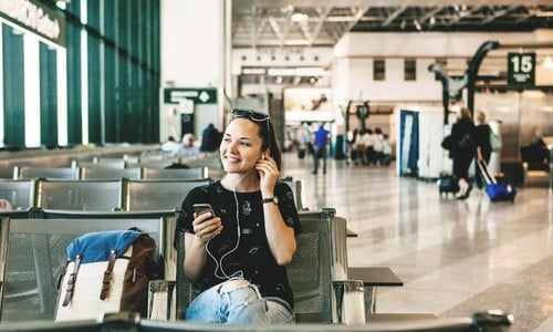 Woman listens to music while waiting for her flight at airport