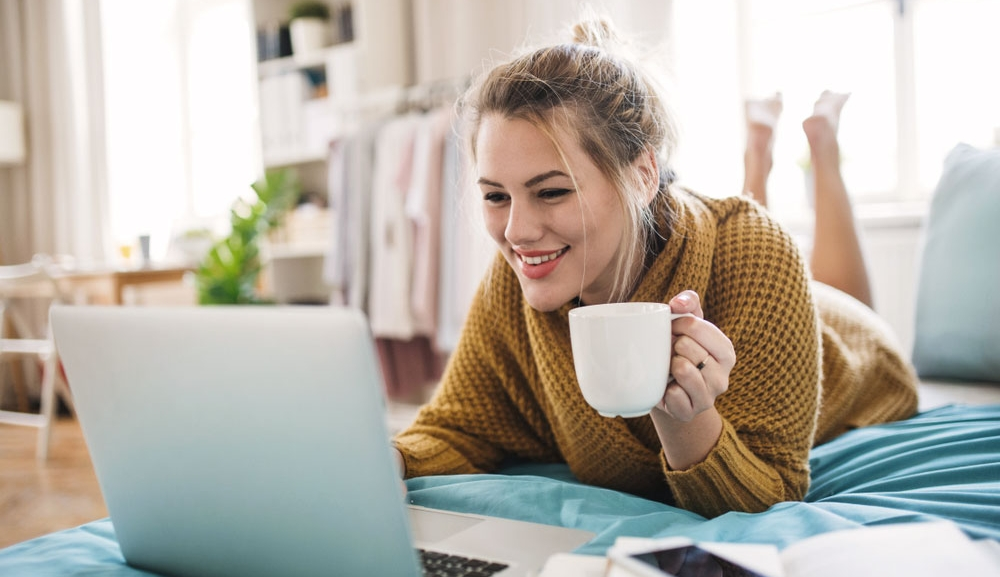 Woman lays on bed casually browsing on her laptop and drinking a coffee