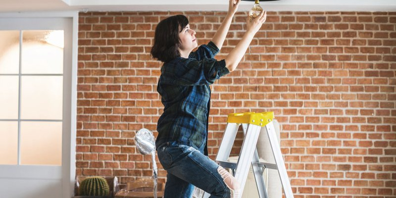 Woman installs modern ceiling light in hip home