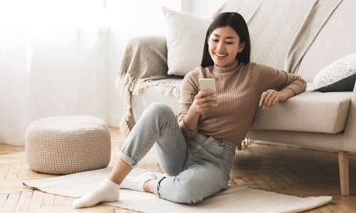Woman sitting on bright living room floor browsing on her phone