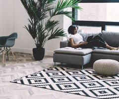 Woman works on her laptop in modern living room with a predominate patterned rug