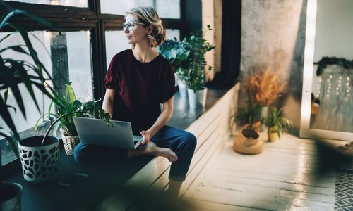 Woman works on her laptop sitting at the window sill in her home with lots of plants around her