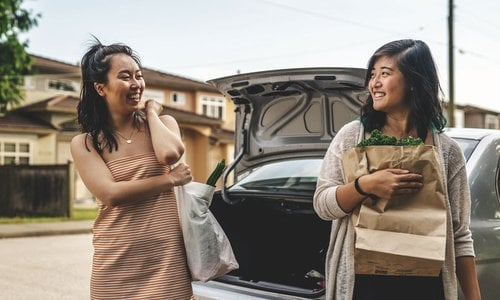 Two female roommates bringing groceries in from their car