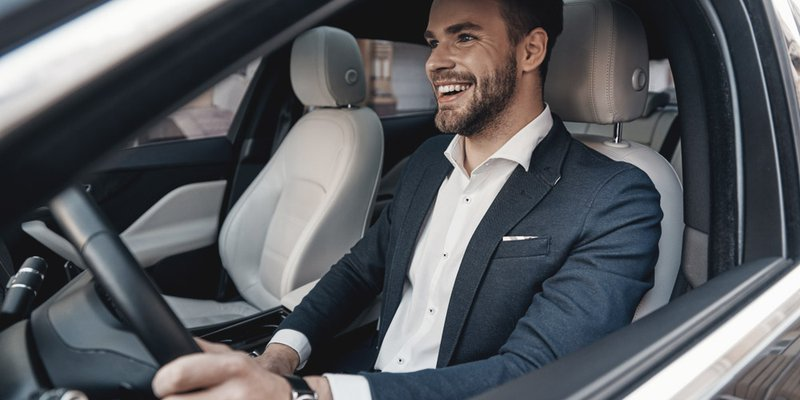 A man in a suit sits smiling in the driver's seat of a vehicle