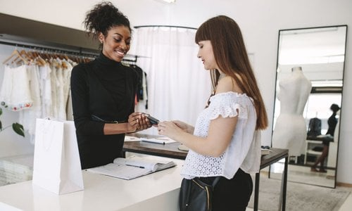 A woman pays for her purchases using her credit card at a boutique