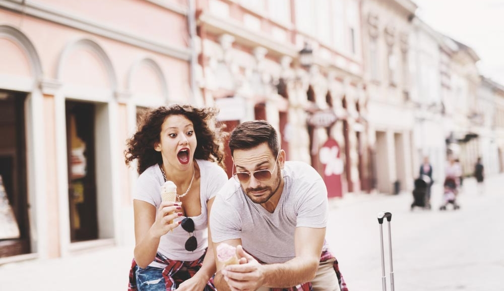 A couple almost loses their ice cream as they walk down the street