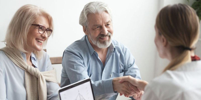 An older couple meet with a realtor who has a home layout pulled up on her computer