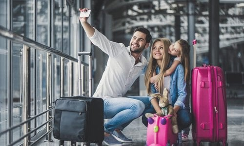 A young family takes a selfie at the airport
