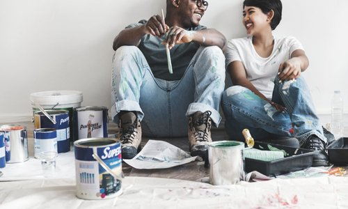 A couple taking a break from painting their house