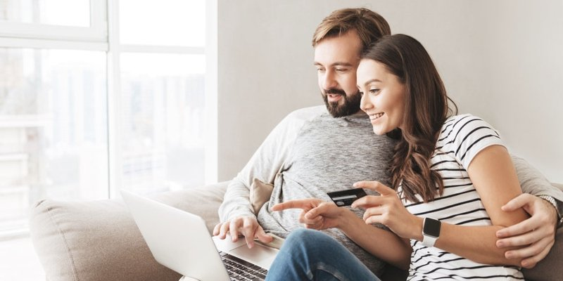 A man and a woman online shop together using a credit card