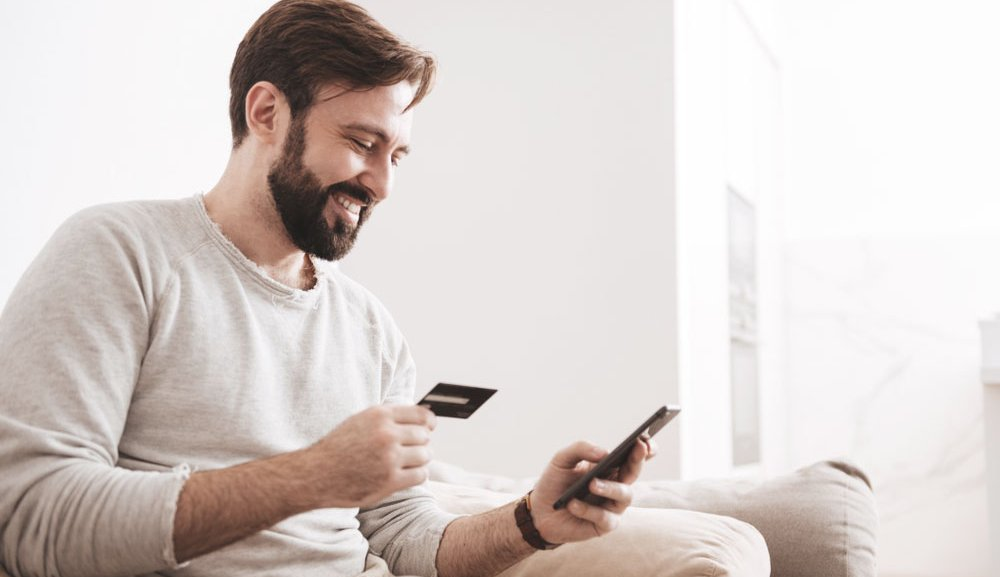 A man sits on a couch and types his credit card details into his phone