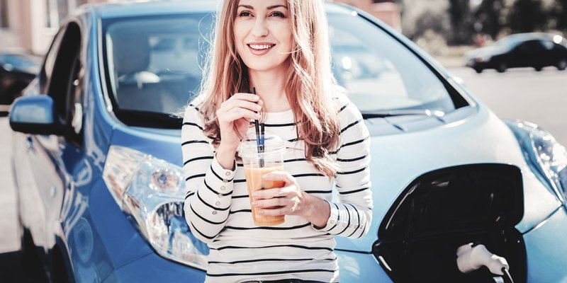 A woman sits on the hood of her blue electric car drinking an iced beverage from a straw