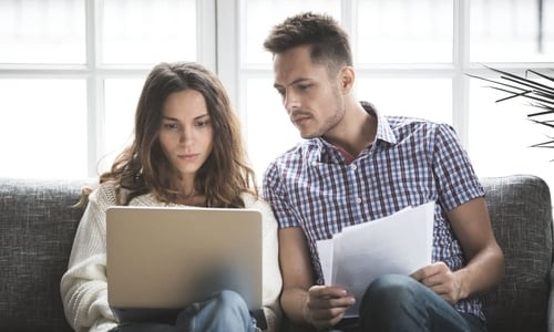 A couple sit together on a couch and review documents while working on a laptop