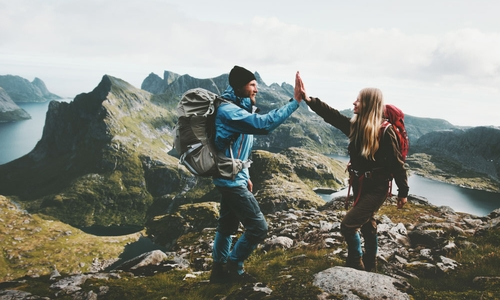 A young couple high five as they reach the mountain top