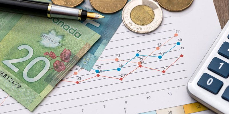 Canadian money spread out around a graph and a calculator