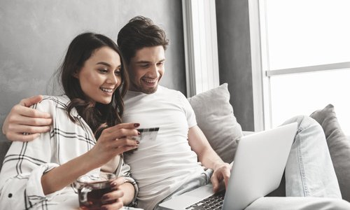 A man and a woman lounge on a couch and online shop together