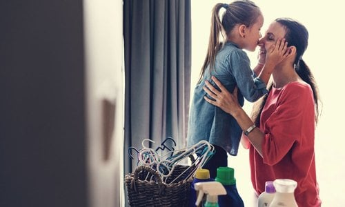 A daughter kisses her mother on the nose while she is doing the laundry