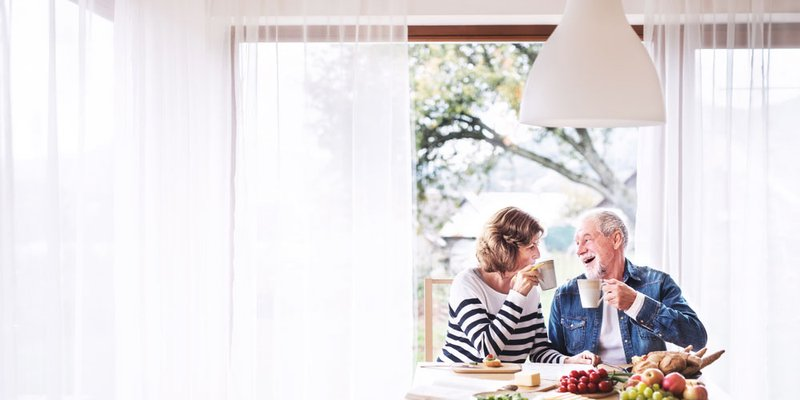 An older couple drink their coffee at the kitchen table