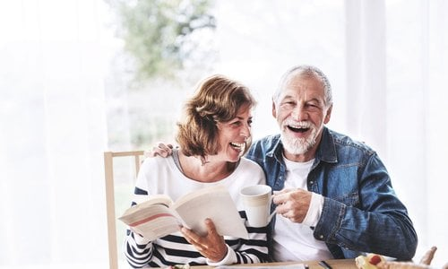 An older couple drink coffee and read a book together at the table
