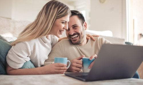 A man and a woman drink coffee together and search for deals on their computer